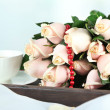 Beautiful bouquet of roses, on wooden tray, on light background — Stock Photo