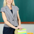 School teacher near table on blackboard background — Foto de Stock