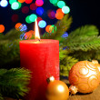 Composition with Burning candle, fir tree and Christmas decorations on multicolor lights background — Stock Photo #37099203