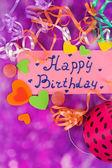 """Karta """"happy birthday"""" obklopen slavnostní prvky na fialovém pozadí — Stock fotografie"""