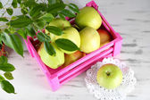 Juicy apples in box on wooden table — Stock Photo