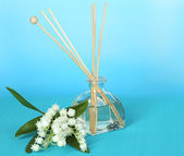 Aromatic sticks for home with floral odor on blue background — Stock Photo