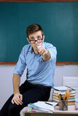Young teacher sitting on desk in school classroom — Stock Photo