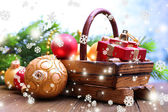 Composition with Christmas decorations in basket, fir tree on wooden table, on light background — Stock Photo