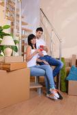 Młoda para siedzi na schodach w nowym domu — Zdjęcie stockowe