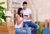 Young couple celebrating moving to new home sitting on stairs — ストック写真