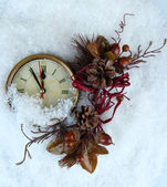 Clock and Christmas decorations under snow close up — Stockfoto