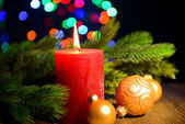Composition with Burning candle, fir tree and Christmas decorations on multicolor lights background — Foto Stock