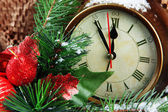 Clock with fir branches and Christmas decoration on brown background — Stock Photo