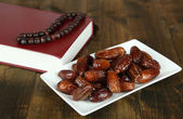 Composition with holy book,rosary and dates palm, on wooden background — Stock Photo
