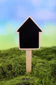 Small chalk board on grass on light background — Stock Photo