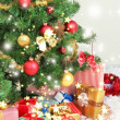 Decorated Christmas tree with gifts on grey wall background — Stock Photo #37104037