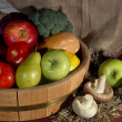 Composition of different fruit and vegetables on table on sackcloth background — Stock Photo #37104553