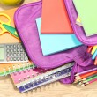 Purple backpack with school supplies on wooden background — Stock Photo #37104831