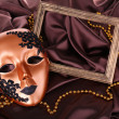 Stock Photo: Mask on brown fabric background