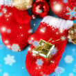 Red winter mittens with Christmas toys on blue wooden table — Stock Photo #37106915