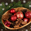 Christmas decorations in basket and spruce branches on wooden background — Stock Photo #37106991