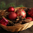 Christmas decorations in basket and spruce branches on wooden background — Stock Photo #37106993