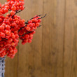 Artificial berries, in wicker vase,  on wooden background — Stock Photo