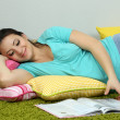 Young pregnant woman lying on floor and reading book on wall background — Stock Photo