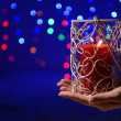 Candle in hand on blur lights background — Stock Photo #37108389