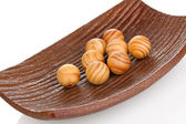 Wooden balls in decorative plate isolated on whit — Stock Photo