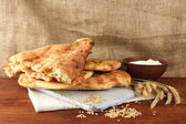 Pita breads with spikes and flour on table on sackcloth background — Stock Photo