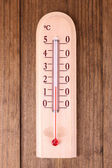 Thermometer on wooden background — Stock Photo