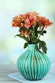 美丽的鲜花插在花瓶里,木制的桌子,在明亮的背景上 — 图库照片