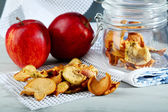 Dried apples in glass jar, on color wooden background — Stock Photo