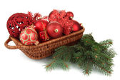 Christmas decorations in basket and spruce branches isolated on white — Stock Photo