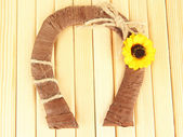 Decorative horseshoe of straw with sunflower, on wooden background — Stock Photo
