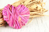 Decorative straw for hand made and heart of straw, on wooden background — Stock Photo