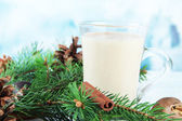 Cup of eggnog with fir branches on table on bright background — Fotografia Stock