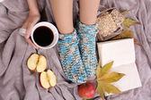 Composition with warm plaid, book, cup of hot drink and female legs, on color carpet background — Foto Stock