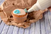 Confectioner decorating tasty cupcake with butter cream, on color wooden background — Foto Stock