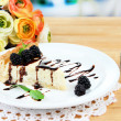 Slice of cheesecake with chocolate sauce and blackberry on plate, on wooden  table, on bright background — Stock Photo