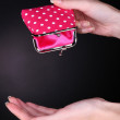 Female hand holding pink purse on black background — Stock Photo