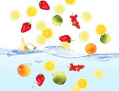 Fresh fruits dropped into water — Stock Photo