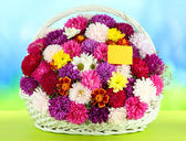 Beautiful bouquet of chrysanthemums in wicker basket on table on bright background — Stock Photo