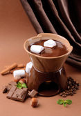 Chocolate fondue with marshmallow candies, on brown background — Stock Photo