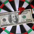 Money pierced by arrow on dartboard close up — Stock Photo