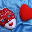 Decorative red heart and mask, on color fabric background — Stock Photo