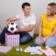 Young pregnant woman with her husband folding baby wear and ball on floor at home — Stock Photo #37205979