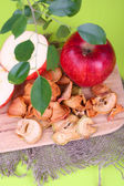 Dried apples, on cutting board, on color wooden background — Stock Photo