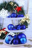 Decorazioni natalizie su dessert stanno, sul colore di sfondo in legno — Foto Stock