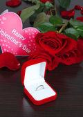 Кольцо, в окружении роз и лепестков на деревянный стол крупным планом — Стоковое фото