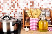 Pot op fornuis in keuken op tafel op mozaïek tegels achtergrond — Stockfoto