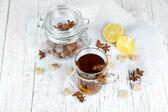 Bevanda calda in tazza di vetro con frutta e spezie, su fondo in legno — Foto Stock