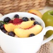Stock Photo: Oatmeal in cup with berries on napkins on wooden table